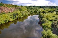 河的两河岸:岩石和简单,用绿草和密集的树盖,在晴朗的天气在多云的蓝色下 免版税库存图片