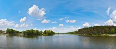 河的全景照片在森林附近的在蓝色多云天空下 库存照片