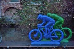 河的塑料骑自行车的人 库存照片