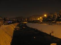 河的夜视图在房子里 库存照片