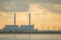 河的工业工厂有在日落的风轮机的 免版税库存图片