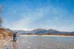 河的河岸的成熟远足者 走往山 库存图片