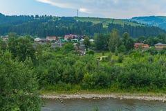 河的流程有石岸的在度假村附近,位于小山的脚 图库摄影