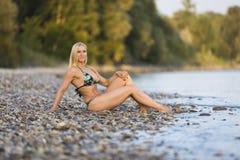 河的白肤金发的比基尼泳装妇女 免版税库存图片