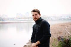 河的背景的英俊的有胡子的人 免版税图库摄影