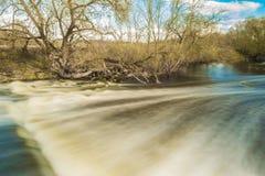 河的迅速流程在树附近通过,并且灌木,冷水落在被毁坏的混凝土白金结构 库存照片