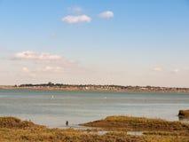 河美好的场面有小船草原的前面蓝天的 免版税图库摄影