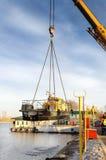 河船运载一台起重机 库存照片