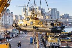 河船运载在四链式吊索的一台起重机 免版税库存照片