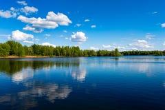 河视图美好的夏天风景与蓝色多云天空和狂放的森林的 免版税库存照片