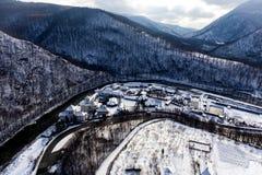 河谷的寄生虫照片通过多雪的山和修道院 免版税库存图片