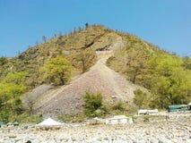 河边岩石、帐篷和山 免版税库存图片