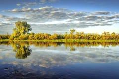 河风景有岸和天空的反射的在水中 分行明亮的开花的绿色本质春天结构树 风景春天河 免版税库存图片