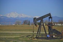 油井,与雪的泵浦起重器加盖了山 免版税库存图片