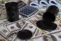 油和桶 在金钱美元货币之上的被倾倒的油 库存图片