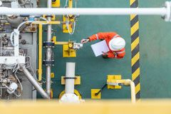 油和煤气产业活动,操作员检查和检查油泵有差别的测量仪和压力传送器作为每日日志表 免版税图库摄影
