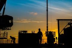 油和煤气泉源平台和好的服务工作者剪影,当工作对穿孔生产管材气体水库时 库存照片