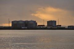 油和煤气的工业贮藏库在日落的港口 免版税库存照片