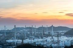 油和煤气精炼厂或石油化学工业在天空日落背景,工厂与晚上,储气球形坦克 免版税库存照片