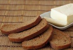 黄油和面包在桌上 库存照片