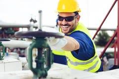 油工作者关闭在输油管的阀门 库存照片