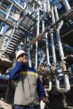 油工作者谈话在精炼厂里面的电话 库存照片