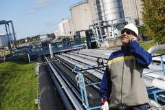 油工作者谈话在精炼厂里面的电话 库存图片