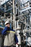 油工作者谈话在精炼厂里面的电话 免版税库存照片