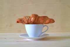 黄油新月形面包正面图与一杯咖啡的 免版税库存图片