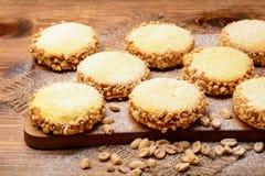 黄油曲奇饼(alfajores)用焦糖和花生在木背景 免版税库存图片