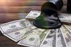 油桶和倾吐的金钱美元货币 图库摄影