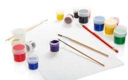 油漆、刷子和铅笔在本文 免版税库存照片