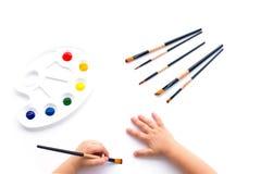 油漆、孩子的刷子和手 免版税库存照片