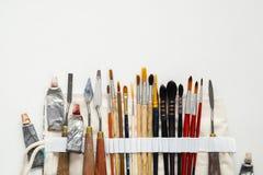 油漆刷、调色刀和油漆管在纺织品运载袋子 存贮事例填装了为专业艺术家工作的工具 免版税库存图片
