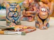 油漆刷、黏土盘区和猫和猴子黏土小雕象  免版税库存照片