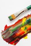 油漆刷和混杂的彩虹油漆在艺术家帆布 免版税库存照片