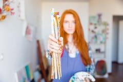 油漆刷由年轻红头发人妇女画家holded在艺术家车间 图库摄影