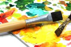 油漆和画笔在调色板 免版税库存图片