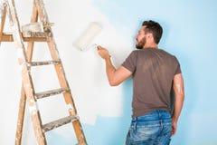 油漆的画家喷溅了绘墙壁的衬衣 免版税库存照片