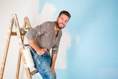 油漆的画家喷溅了绘墙壁的衬衣 库存照片