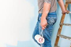 油漆的画家喷溅了绘墙壁的衬衣 免版税库存图片