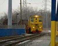 柴油火车和工作者走的铁路在多雪的冬日 免版税图库摄影