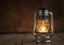 油灯在晚上在木表面 库存照片