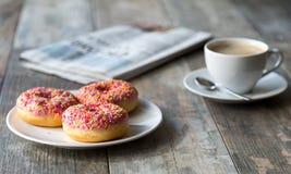 油炸圈饼、咖啡和报纸 库存图片