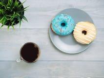 油炸圈饼和咖啡在灰色木背景,拷贝空间,顶视图 免版税库存图片