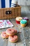 油炸圈饼和杯形蛋糕在木桌上 库存图片