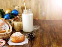 油炸圈饼柏林人和圣诞节属性牛奶围拢的一个玻璃瓶子 免版税库存图片