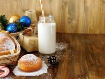 油炸圈饼柏林人和圣诞节属性牛奶围拢的一个玻璃瓶子 库存照片