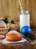 油炸圈饼柏林人和圣诞节属性牛奶围拢的一杯 免版税库存图片