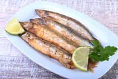 油炸小鱼毛鳞鱼和切的柠檬在白色板材 对啤酒的好快餐 库存图片